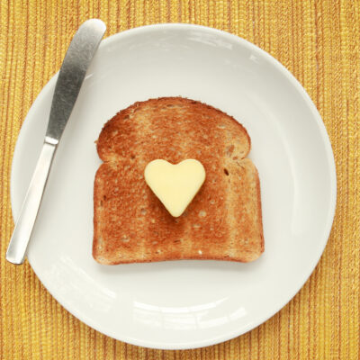 A piece of toast on a plate with a heart shaped pat of butter
