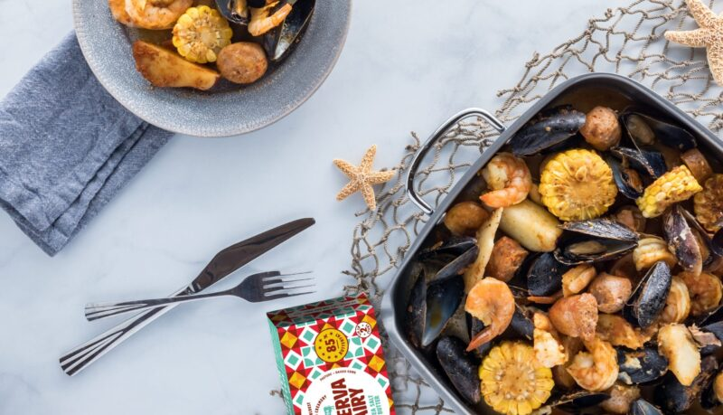 New England clam bake in a roasting pan with a serving of it ready to eat.